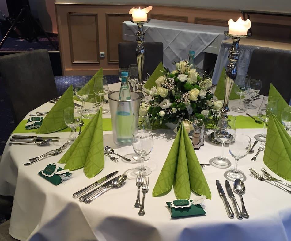 Auf dem Bild ist ein gedeckter Tisch für ein Event zu sehen.